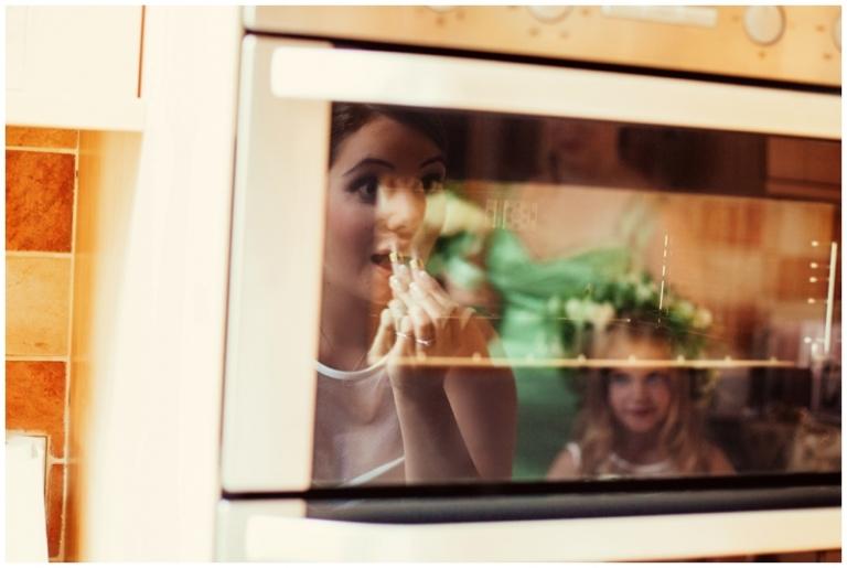 bride putting on lipstick oven door mirror